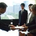 要請者と手交する日弁連の神副会長(右)と小川司法法制部長。
